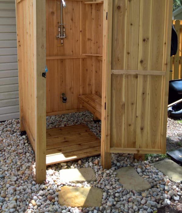 An outdoor shower with beach pebbles for drainage